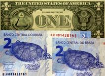 Imagen ilustrativa realizada en Sao Paulo de unos billetes de dos reales y uno de un dólar , sep 22, 2015. Brasil lanzará el jueves un bono referencial en dólares al 2026, dijo el Ministerio de Hacienda en un comunicado.   REUTERS/Paulo Whitaker
