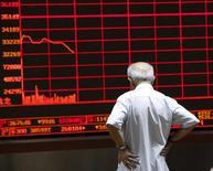Un inversor mira un panel electrónico que muestra información bursátil, en una correduría en Pekín, China, 7 de julio de 2015. Las acciones chinas cerraron el viernes con una leve ganancia, revirtiendo unas pérdidas iniciales, luego de que el sector bancario recuperó algo de terreno en las operaciones de la tarde. REUTERS/Kim Kyung-Hoon
