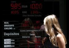 Una mujer camina junto a un panel que muestra la tasa cambiaria entre varias divisas, en una casa de cambio en el distrito financiero de Buenos Aires, Argentina. 16 de diciembre de 2015. Las compañías estadounidenses seriamente afectadas por una devaluación del 37 por ciento en el peso argentino están apostando a realizar más negocios en el país sudamericano, confiadas en que el sacudón a corto plazo por la liberalización de la economía abrirá paso a ganancias en un futuro más lejano. REUTERS/Marcos Brindicci