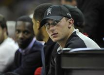 Cleveland Browns quarterback Johnny Manziel watches the game from the front row in the second quarter at Quicken Loans Arena, in Cleveland, Ohio, in this October 17, 2014 file photo.    REUTERS/David Richard-USA TODAY Sports