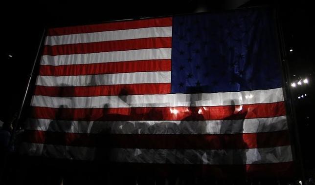 3月8日、世界各国の中央銀行が失敗に終わったことが、米大統領選によって実現されるかもしれない。ただ希望したやり方ではない。「保護主義」によるインフレの回復だ。写真は米フロリダ州のマイアミで、バーニー・サンダース候補の支持者が掲げた米国国旗。8日撮影(2016年 ロイター/Carlo Allegri)