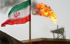 Иранский флаг на нефтедобывающей платформе в Персидском заливе. 25 июля 2005 года. Иран присоединится к переговорам нефтедобывающих стран о заморозке объемов производства только после того, как его собственная добыча достигнет 4 миллионов баррелей в сутки, сообщило в воскресенье иранское новостное агентство ISNA со ссылкой на министра нефти страны Биджана Зангане. REUTERS/Raheb Homavandi