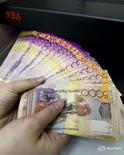 Кассир проверяет купюры валюты тенге вотделении Казкоммерцбанка в Алма-Ате 4 февраля 2010 года. Нацбанк Казахстана сообщил в понедельник о сохранении базовой ставки на уровне 17 процентов, говорится в сообщении Нацбанка. REUTERS/Shamil Zhumatov