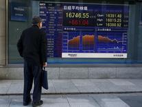 Un hombre mira un tablero electrónico que muestra el índice Nikkei, afuera de una correduría en Tokio, Japón. 2 de marzo de 2016. Las acciones japonesas tocaron máximos de una semana el lunes, luego de que los inversores dejaron atrás un escepticismo inicial sobre el último paquete de estímulo del Banco Central Europeo (BCE). REUTERS/Thomas Peter