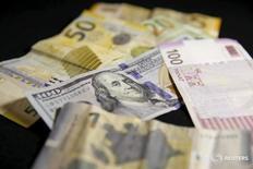 Купюры валют доллар США и манат в Тбилиси 15 января 2016 года. Центральный банк Азербайджана сообщил во вторник, что сумел предотвратить ажиотаж на валютном рынке страны, а экономические субъекты начали постепенно привыкать к новому режиму, предусматривающему плавающий курс маната. REUTERS/David Mdzinarishvili