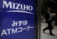 A man walks past a signboard of Mizuho Bank ATM outside its headquarters in Tokyo, Japan, November 12, 2015. REUTERS/Yuya Shino