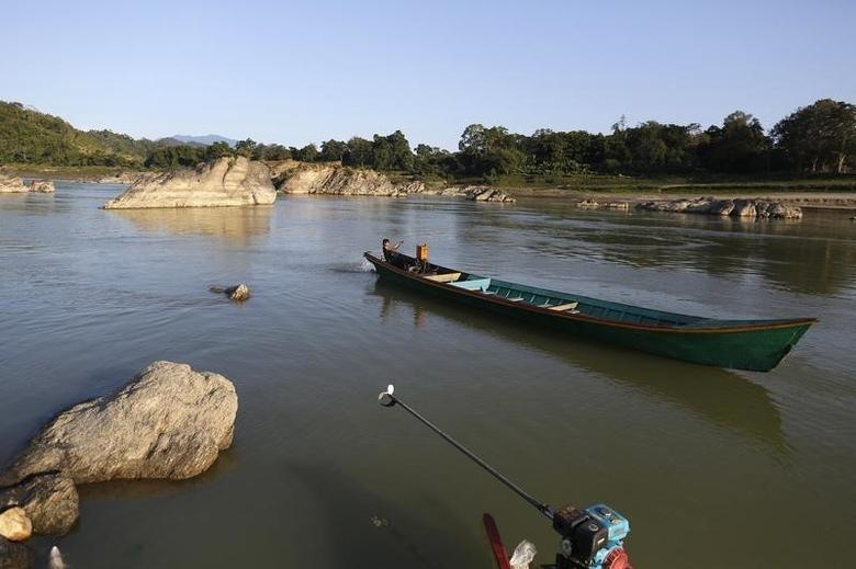 A man steers his boat at Myitsone, outside Myitkyina, the capital city of Kachin state, in northern Myanmar December 18, 2014.  REUTERS/Soe Zeya Tun