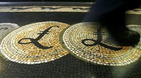 Los responsables de política monetaria del Banco de Inglaterra dijeron que la libra esterlina se ha visto vapuleada por la incertidumbre de que el referéndum sobre la permanencia del Reino Unido en la UE pueda ralentizar el crecimiento, tras votar unánimemente por mantener los tipos de interés en el mínimo histórico del 0,5 por ciento. En la imagen, un empleado pisa un mosaico con el símbolo de la libra  en la entrada del Banco de Inglaterra en Londres, el  25 de febrero de 2008. REUTERS/Luke MacGregor/Files