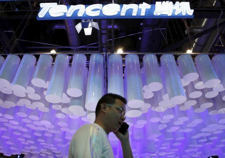 A man uses a mobile phone in front of a logo of Tencent at the Global Mobile Internet Conference (GMIC) 2015 in Beijing, China, April 28, 2015. REUTERS/Kim Kyung-Hoon
