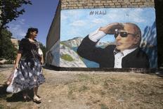 Женщина проходит мимо граффити с изображением президента России Владимира Путина в крымском Симферополе 21 августа 2015 года. Путин в пятницу побывает в Крыму, сообщили российские информагентства в четверг со ссылкой на пресс-службу Кремля. REUTERS/Pavel Rebrov