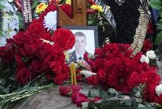 A view shows the grave of Russian serviceman Fyodor Zhuravlyov after the funeral at a cemetery in the village of Paltso, Bryansk region, Russia, November 24, 2015. Zhuravlyov left home in a rush. He only managed to scrawl a phone number and a few words to his wife on a sheet of paper. Late last week the military contacted the family to say that he was killed in combat on Thursday, Nov. 19. The 27-year-old now joins the growing ranks of the Russian army's unexplained dead, victims of the Kremlin's military engagements inside Russia and, in the past few years, beyond its borders too that are so secretive nobody will officially acknowledge where the deaths have occurred. Picture taken November 24, 2015. REUTERS/Maria Tsvetkova
