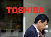 Homem passa em frente a fachada com logo da Toshiba. 30 de setembro de 2015. REUTERS/Toru Hanai/Files