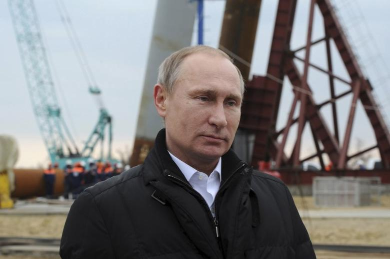 Russian President Vladimir Putin via a video link addresses people marking the second anniversary of Russia's annexation of the Crimea region in Moscow's Red Square, as he visits the construction site of the transport passage across the Kerch Strait on Tuzla island near the Black Sea port of Kerch, Crimea, March 18, 2016. REUTERS/Mikhail Klimentyev/Sputnik/Kremlin