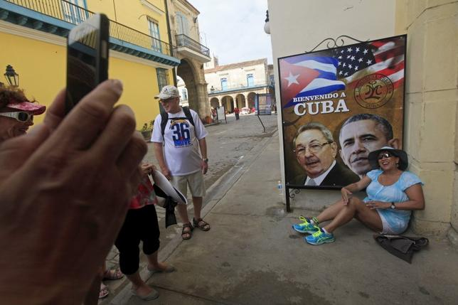 A visitor from California has her picture taken by a travel companian next to images of Cuba's President Raul Castro and U.S. President Barack Obama in Havana, Cuba March 19, 2016. The headline on the poster reads: ''Welcome to Cuba.'' REUTERS/Enrique De La Osa