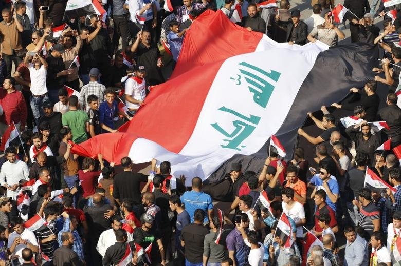 Supporters of prominent Iraqi Shi'ite cleric Moqtada al-Sadr display a huge Iraqi flag during a protest against government corruption at Tahrir Square in Baghdad, Iraq March 11, 2016. REUTERS/Ahmed Saad