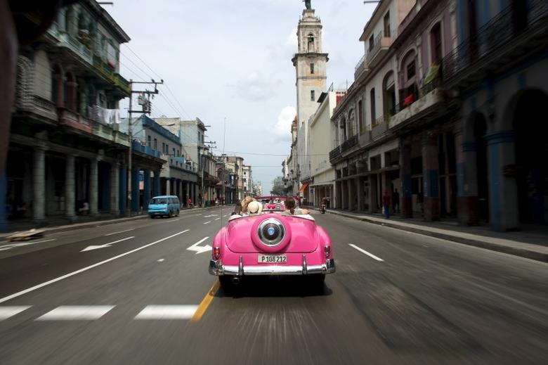 Tourists ride in a vintage car in Havana, March 19, 2016.  REUTERS/Alexandre Meneghini