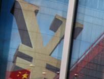 """Una bandera nacional de China se reflejan en la publicidad de un banco comercial que muestra el signo del Yuan, en un distrito financiero en Pekín, China, 21 de enero de 2016. China considera aplicar un """"impuesto Tobin"""" como posible herramienta de política para limitar las salidas de capitales, dijo el martes un funcionario del regulador cambiario del país, incluso a pesar de que agregó que tales flujos han bajado en meses recientes. REUTERS/Kim Kyung-Hoon"""