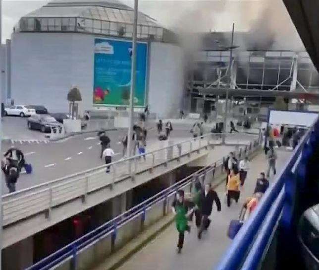 People flee from the Brussels airport in this image taken from video, shot by a bystander in the the immediate aftermath of blasts at the airport near Brussels, Belgium, March 22, 2016.  REUTERS/Asher  Gunsberg/Handout via Reuters TV