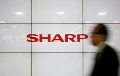 Un hombre pasa frente a un cartel con el logo de Sharp Corp en Tokio, Japón, el 25 de febrero de 2016. La firma taiwanesa de tecnología Foxconn quiere reducir su oferta por la japonesa Sharp Corp en al menos 100.000 millones de yenes (893 millones de dólares) para cubrir probables ganancias anuales peores a lo previsto y riesgos revelados hace poco en la empresa de electrónica, dijeron dos fuentes el martes. REUTERS/Yuya Shino