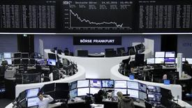 Las acciones europeas cayeron el martes, con los títulos de firmas relacionadas con los viajes y el ocio presionando al mercado tras los mortales atentados con bomba en Bruselas. En la imagen, operadores trabajan en sus mesas delante del índice de precios alemán DAX en la bolsa de Fráncfort, Alemania, el 24 de febrero de 2016.     REUTERS/Staff/Remote