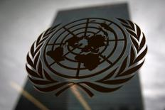 The United Nations headquarters building is pictured though a window with the UN logo in the foreground in the Manhattan borough of New York August 15, 2014.    REUTERS/Carlo Allegri