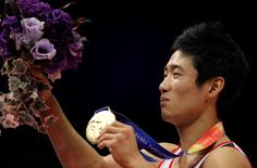 Gold medalist Yang Hak-seon of South Korea shows his medal on the podium during an awarding ceremony after competed on the vault at men's apparatus final at the Artistic Gymnastics World Championships in Tokyo October 16, 2011.   REUTERS/Toru Hanai