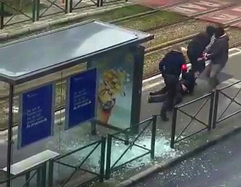 Belgian police drag a suspect along a tramway platform, in this still image taken from amateur video, after the suspect was shot, in the Brussels borough of Schaerbeek, following Tuesday's bombings in Brussels, Belgium, March 25, 2016.     Sudpresse via REUTERS