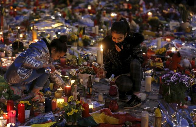 Girls light candles as people pay tribute to the victims of Tuesday's bomb attacks, at the Place de la Bourse in Brussels, Belgium, March 26, 2016. REUTERS/Christian Hartmann