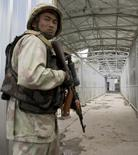 Узбекский пограничник у пункта пропуска на границе с Киргизией на мосту через реку Кара-Су 16 июня 2010 года. Киргизия и ее более мощный сосед по Центральной Азии Узбекистан ослабили напряженность на спорном участке границы, отведя войска и бронетехнику после встречи глав погранслужб, сообщил Бишкек. REUTERS/Shamil Zhumatov