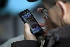 Мужчина изучает информацию о котировках на экране мобильного телефона в Шанхае 7 марта 2016 года. Китайский фондовый рынок сдал завоеванные ранее позиции и завершил торги снижением основных индексов, после того как падение акций компаний сектора недвижимости во второй половине дня свело на нет первоначальный оптимизм инвесторов, вызванный вдохновляющими данными о прибыли промышленных предприятий. REUTERS/Aly Song