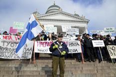 Фермер Микко Лахтилуома (в центре) держит финский флаг на акции протеста с участием свыше 5.000 фермеров в Хельсинки 11 марта 2016 года. Финны испытывают на себе выписанный грекам рецепт экономии. REUTERS/Tuomas Forsell