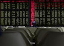 Un inversor mira un tablero electrónico que muestra información bursátil, en una correduría en Pekín, China, 25 de agosto de 2015. Las acciones chinas cedieron unas ganancias iniciales, luego de que un declive al final de la sesión de los valores ligados al sector inmobiliario borró el optimismo inicial provocado por unos datos positivos reportados el fin de semana. REUTERS/Kim Kyung-Hoon