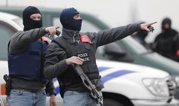 Скрывшие лица масками бельгийские полицейские у Дворца правосудия в Брюсселе 24 марта 2016 года. Бельгия освободила подозреваемого во взрывах в аэропорту из-за отсутствия улик. REUTERS/CHRISTIAN HARTMANN