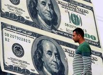 En la imagen, un hombre pasa frente a un cartel publicitario de una oficina de cambio de divisas, en cuya fachada se aprecia la imagen del dólar, en el Cairo, Egipto, el 21 de febrero de 2016. El dólar retrocedía el lunes frente a una canasta de monedas relevantes, luego de que datos de Estados Unidos que mostraron un retroceso en la inflación y una revisión a la baja en el gasto de los consumidores dañaron la expectativa de un ritmo más acelerado de alza en la tasa de interés por parte de la Fed. REUTERS/Mohamed Abd El Ghany