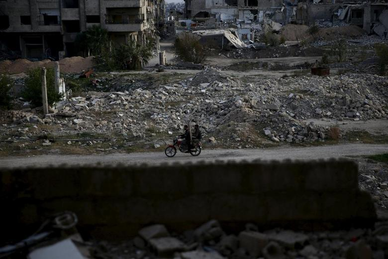 Men ride a motorbike near damaged buildings in the rebel-controlled area of Jobar, a suburb of Damascus, Syria March 23, 2016. REUTERS/Bassam Khabieh