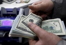 Imagen de archivo de un cajero contando dólares en una casa de cambios en Estambul, abr 15, 2015. El dólar subía contra el yen el martes, con el foco puesto en un discurso de la presidenta de la Reserva Federal, Janet Yellen, quien podría dar pistas sobre cuándo podrían subir las tasas de interés este año.  REUTERS/Murad Sezer
