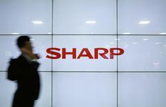 A man using his mobile phone walks past Sharp Corp's liquid crystal display monitors showing the company logo in Tokyo, Japan, March 30, 2016. REUTERS/Yuya Shino