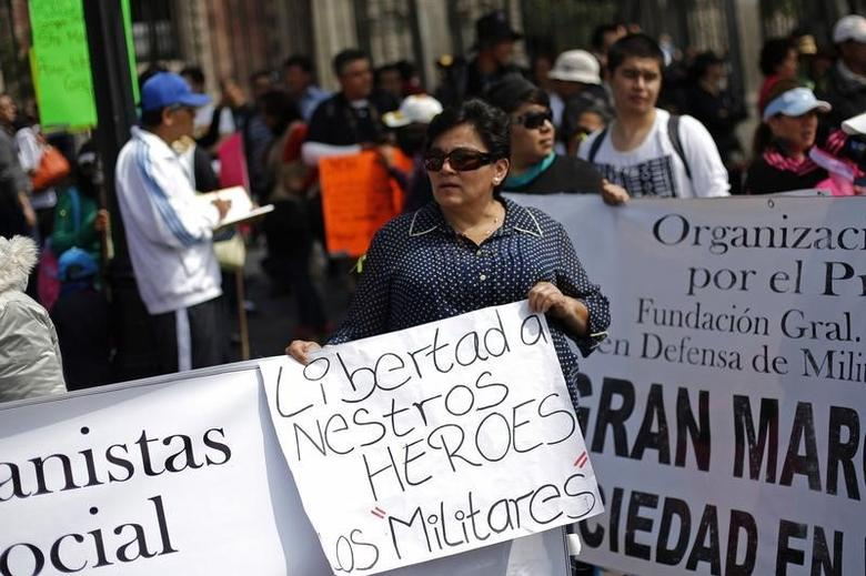 A relative of soldiers accused of homicide holds a sign during a protest against the government in Mexico City October 11, 2014. REUTERS/Bernardo Montoya