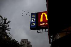 Birds fly past a sign of 24-hour McDonald's restaurant at sunrise in Hong Kong, China November 11, 2015. REUTERS/Tyrone Siu