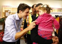Syrian refugees are greeted by Canada's Prime Minister Justin Trudeau (L) on their arrival from Beirut at the Toronto Pearson International Airport in Mississauga, Ontario, Canada December 11, 2015. REUTERS/Mark Blinch
