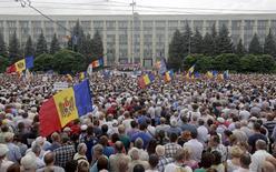 Протестующие держат в руках национальные флаги Молдавии на антиправительственной акции в центре Кишинева 6 сентября 2015 года. REUTERS/Valery Korchmar