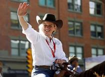 Rachel Notley (L) waves to the crowd while riding a horse during the Calgary Stampede parade in Calgary, Alberta, July 3, 2015. REUTERS/Todd Korol