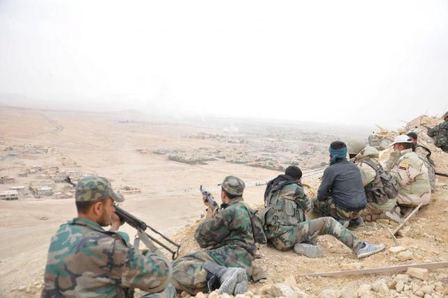 Forces loyal to Syria's President Bashar al-Assad take positions on a look-out point overlooking the historic city of Palmyra in Homs Governorate in this handout picture provided by SANA on March 27, 2016. REUTERS/SANA/Handout via Reuters