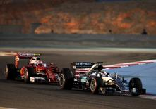 Formula One - Bahrain F1 Grand Prix - Sakhir, Bahrain - 02/04/16 - Mercedes F1 driver, Lewis Hamilton of Britain (L) and Ferrari F1 driver, Kimi Raikkonen of Finland drive during qualifying session for Bahrain F1 GP. REUTERS/Hamad I Mohammed