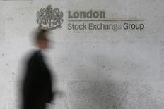 Человек проходит мимо логотипа Лондонской фондовой биржи 11 октября 2013 года. Фондовые индексы Европы упали практически до месячного минимума в понедельник на фоне снижения акций телекомов из-за провалившихся переговоров операторов связи Orange и Bouygues. REUTERS/Stefan Wermuth