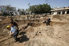 Palestinian boys look on in front of an excavator at the site where ancient ruins, which archaeologists say may be part of a Byzantine church or cathedral dating from around 1,500 years ago, were found in Gaza City April 4, 2016. REUTERS/Mohammed Salem