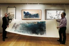 "An inkbrush painting by late Chinese artist Zhang Daqian called ""Peach Blossom Spring"" is rolled during a preview at Sotheby's in Hong Kong, China, in this March 10, 2016 file photo. REUTERS/Bobby Yip/Files"