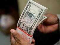 Una persona revisando billetes de 5 dólares en la Casa de la Moneda estadounidense en Washington, abr 15, 2015. La apreciación del dólar que se inició a mediados de 2014 ya casi ha agotado su curso y retomará fuerza sólo levemente durante el año próximo, según un sondeo de Reuters entre estrategas, quienes afirmaron que los riesgos a sus pronósticos están más inclinados hacia la baja.  REUTERS/Gary Cameron