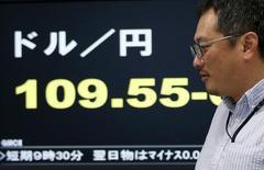 Электронное табло в Токио, демонстрирующее курс иены к доллару. Подъем на фондовых рынках и предупреждение японского министра финансов о возможной интервенции центробанка остановили в пятницу рост курса иены, наблюдавшийся на протяжении недели. REUTERS/Issei Kato