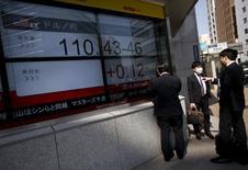 Personas miran un tablero electrónico que muestra información bursátil, en Tokio, Japón. 6 de abril de 2016. La mayoría de las bolsas de Asia caía a mínimos de tres semanas el viernes, pero Japón rompía la tendencia después de que su ministro de Finanzas se comprometió a tomar medidas para contrarrestar los movimientos fuertes del yen en una u otra dirección. REUTERS/Issei Kato
